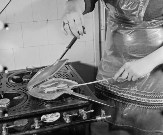 1960 - Alumínium szalonnasütő tűzbiztonságilag aggályos nejlonköténnyel. Forrás: Fortepan, Bauer Sándor